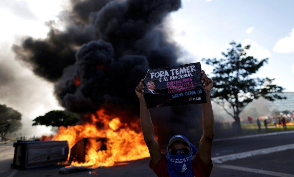 Manifestante com cartaz contra o presidente Temer, diante de uma barricada em Brasília.
