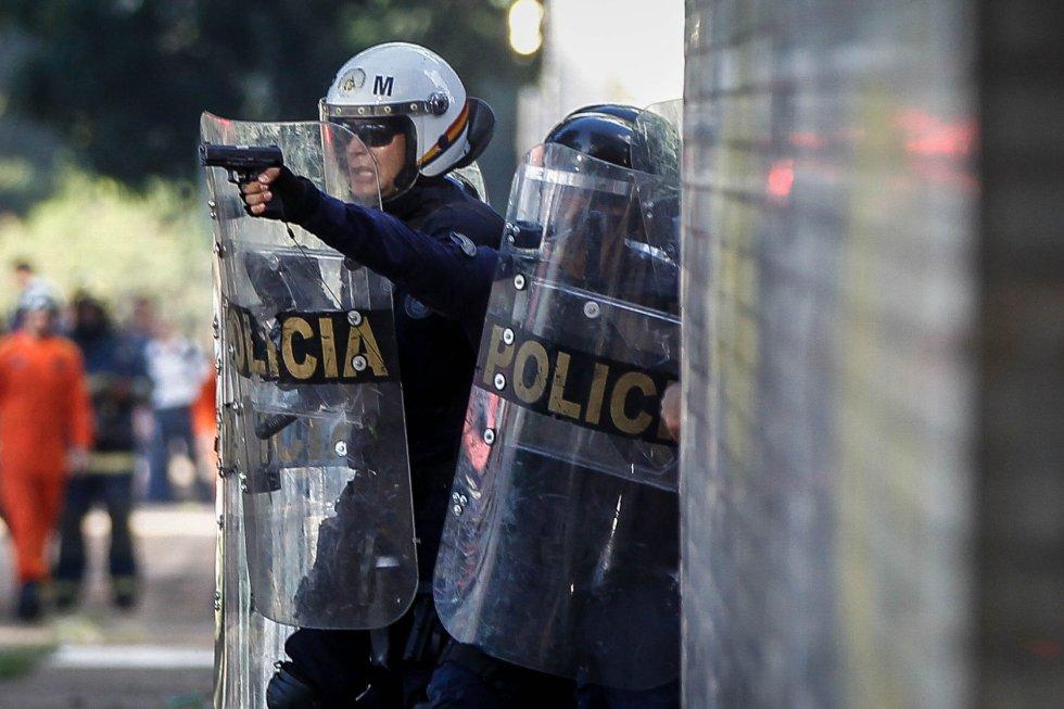 PM aponta arma para manifestantes durante protesto contra o Governo Temer, na Esplanada dos Ministérios.