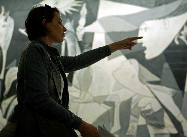 Una espectadora pasa ante el Guernica, de Pablo Picasso
