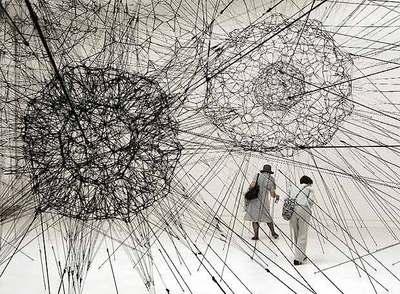 Dos mujeres pasan bajo la instalación del artista argentino Tomás Saraceno en la Bienal de Venecia