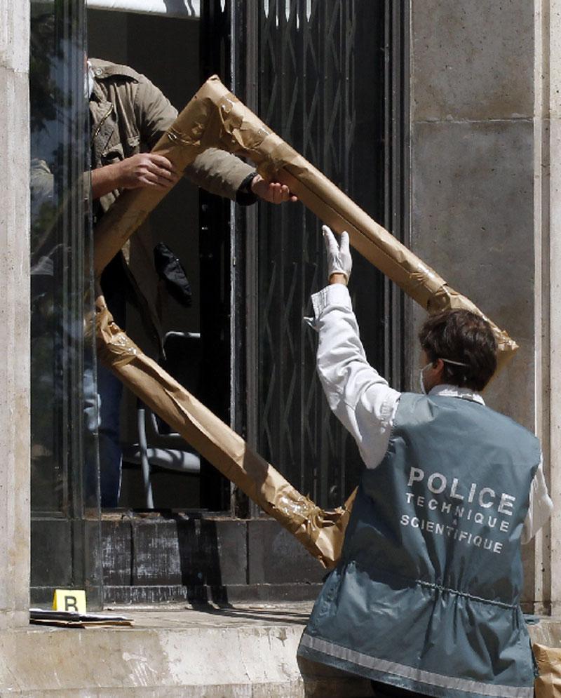 En la imagen, un policía científico saca del museo uno de los marcos de las obras robadas