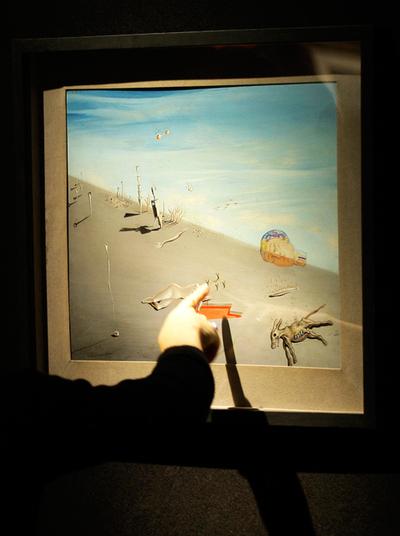 Un empleado de Christie's señala un detalle del estudio de Dalí 'La miel es más dulce que la sangre'.- EFE