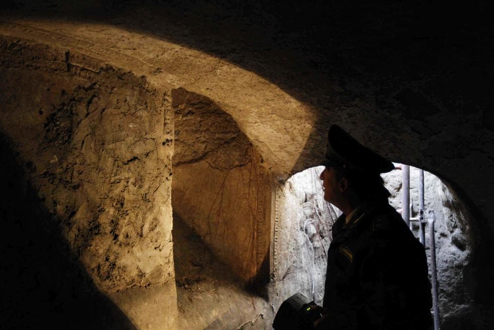 Un policía italiano ilumina con una linterna una pared de un mausoleo del siglo II d. C., cuyo acceso estaba oculto bajo la basura de un vertedero ilegal en Nápoles. (FOTOS: CIRO DE LUCA, AGN FOTO)