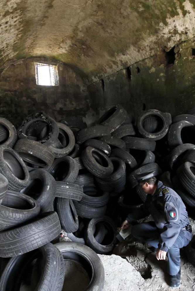Un policía mira el acceso subterráneo al mausoleo, ante una gran masa de neumáticos.