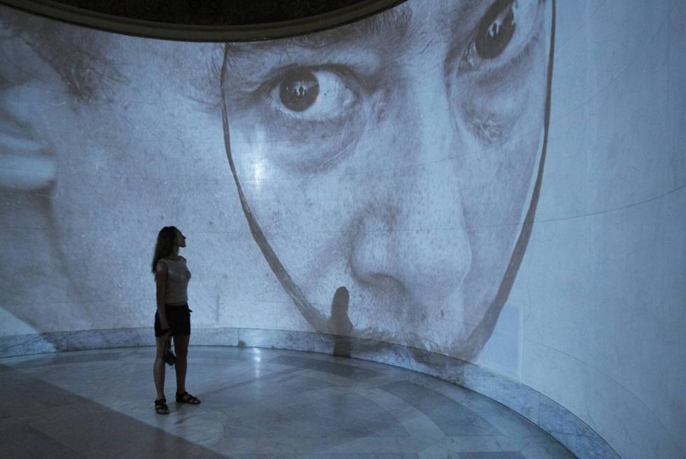 Dalí, a lo grande. Una visitante mira la proyección de una imagen de Salvador Dalí, durante la presentación de una nueva exposición de su obra en el Museo Pushkin de Moscú. SERGEI KARPUKHIN (REUTERS)
