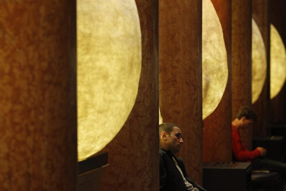 Dos visitantes descansan sentados en unos bancos, en la exposición que el Museo Pushkin de Moscú dedica a Salvador Dalí. SERGEI KARPUKHIN (REUTERS)