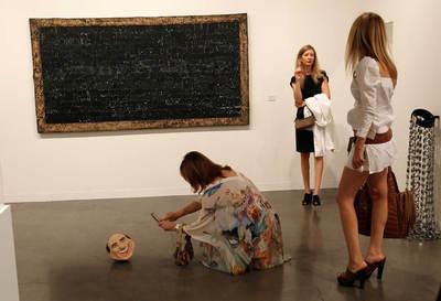 La artista radicada en Nueva York Miru Kim yace junto a dos cerdos en un cercado de cristal como parte de la instalación artística 'Me gustan los cerdos y a los cerdos les gusto (104 horas)' efectuada en la feria de arte contemporáneo Art Basel de Miami- HANS DERYK (REUTERS)