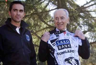 Contador, junto a Simon Peres, que sujeta el maillot firmado por todo el Saxo Bank.