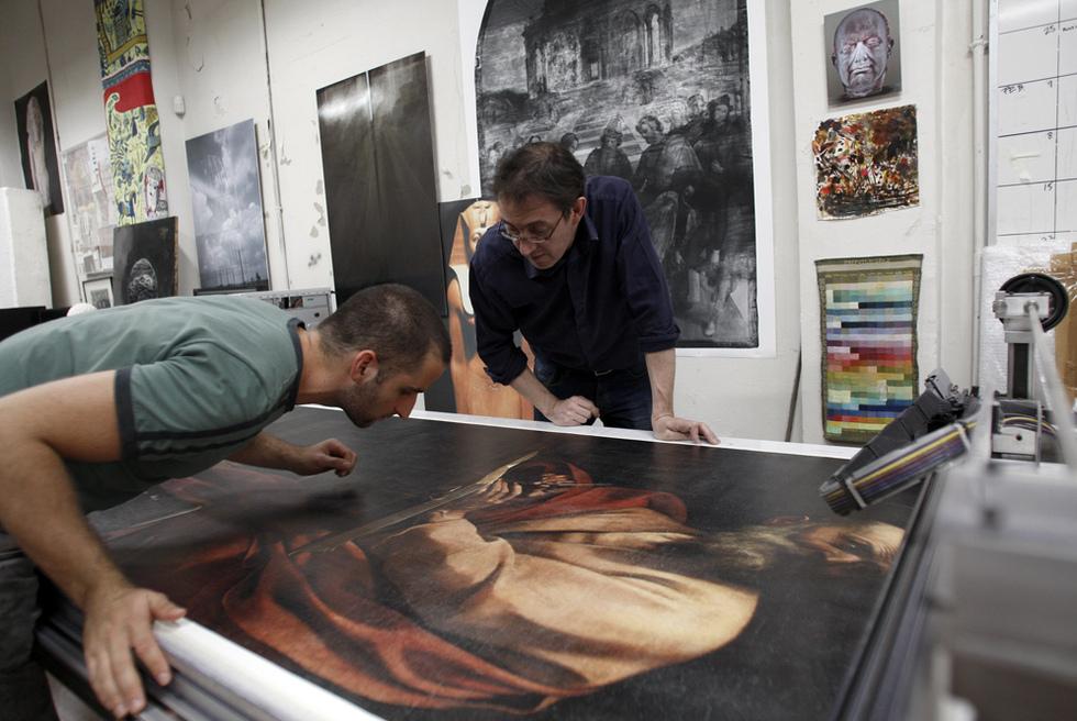 Adam Lowe (a la derecha) y uno de sus colaboradores revisan en el escáner la copia impresa de San Mateo y el ángel, de Caravaggio.- LUIS SEVILLANO