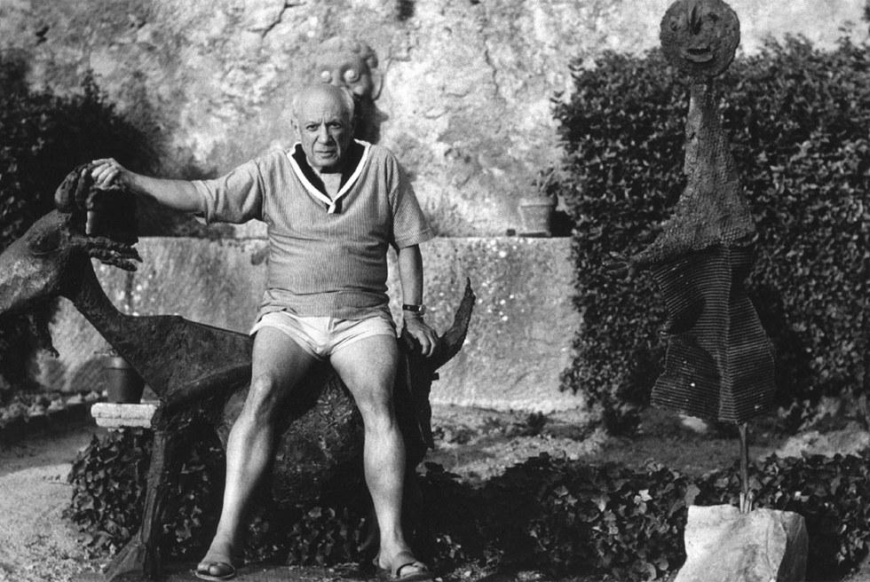 Picasso, sentado sobre La cabra (1950) en Vauvenargues. A su izquierda, El orador (1933). / roberto otero, museo picasso málaga- BANCO DE IMÁGENES DE VEGAP