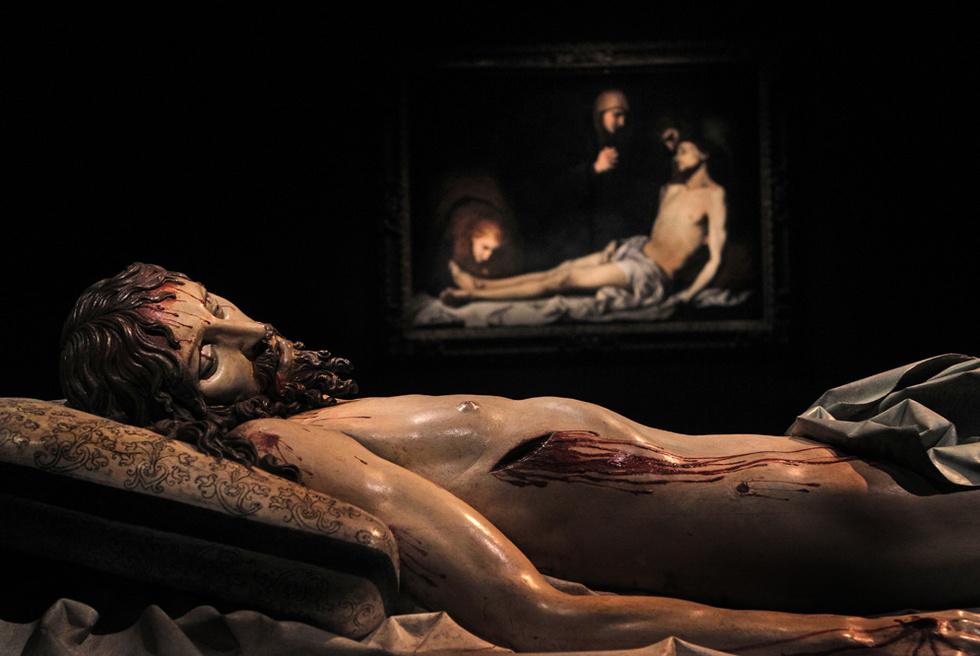 Cristo yacente, escultura policromada de Gregorio Fernández, y, al fondo, Lamento por el Cristo muerto, de Ribera. Piezas de la muestra Lo sagrado hecho real, en Valladolid.- ULY MARTÍN