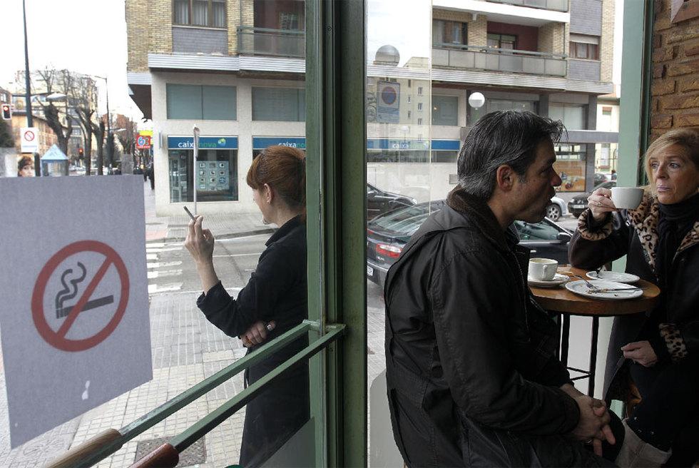 Una mujer fuma en la puerta de un bar