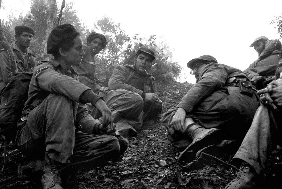 Ernesto Che Guevara, fumando una pipa, y Fidel Castro, a su izquierda, en Sierra Maestra, en septiembre de 1957.- ENRIQUE MENESES