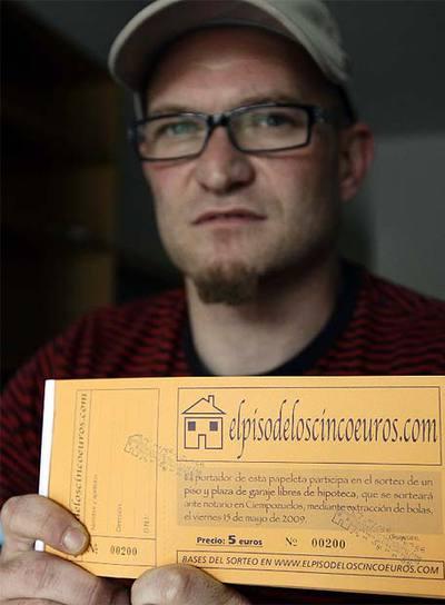 Miguel Marina muestra las papeletas de la rifa, con la que pretende deshacerse de un piso que no puede pagar.- REUTERS