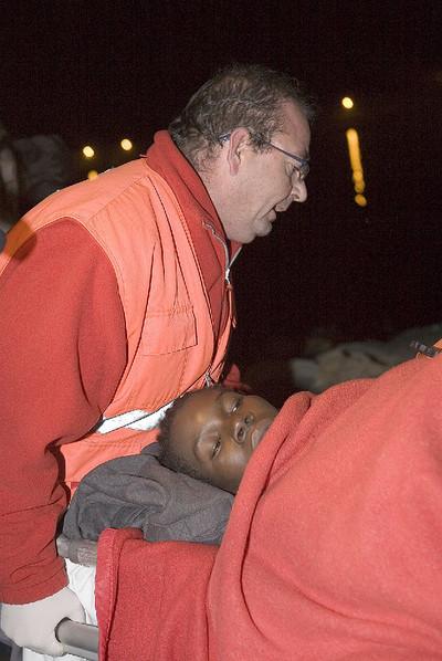 La enfermera de Cruz Roja de Motril Luisa Ferriz (derecha) entrega a una voluntaria a la pequeña Happiness, nacida en una patera en la isla de Alborán.- EFE