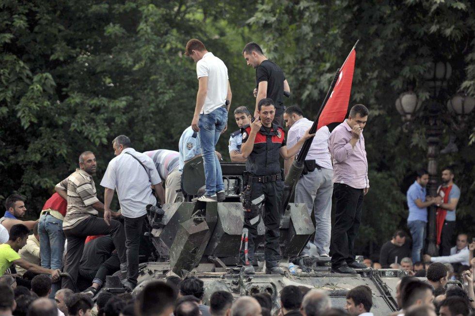Un policía turco y un grupo de personas toman un vehículo militar en Ankara.