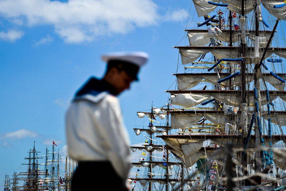 Un marinero delante de varios barcos de vela amarrados en el muelle de Santa Apolonia en Lisboa, Portugal.