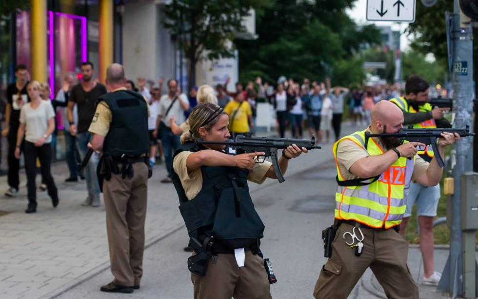 Los agentes de policía apuntan con sus armas de fuego hacia el centro comercial Olympia Einkaufzentrum, mientras son evacuados las personas que se encontraban en dicho centro.