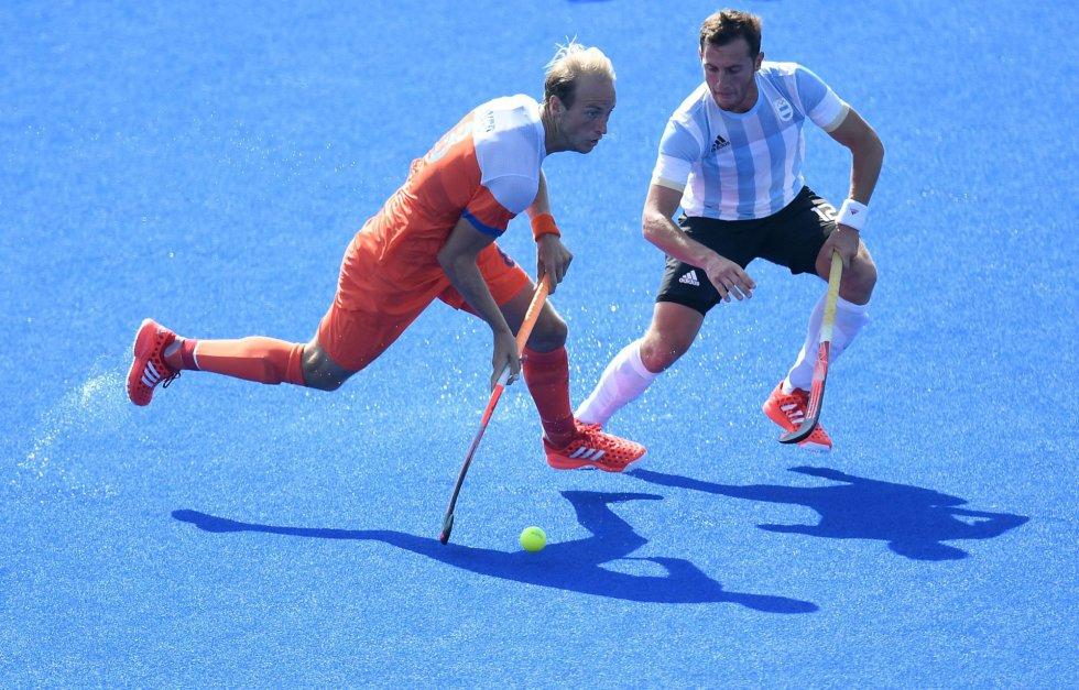 Billy Bakker (e), da Holanda, controla a bola diante de Lucas Vila, da Argentina, numa partida de hóquei sobre grama no Centro Olímpico de Hóquei, no Rio de Janeiro.