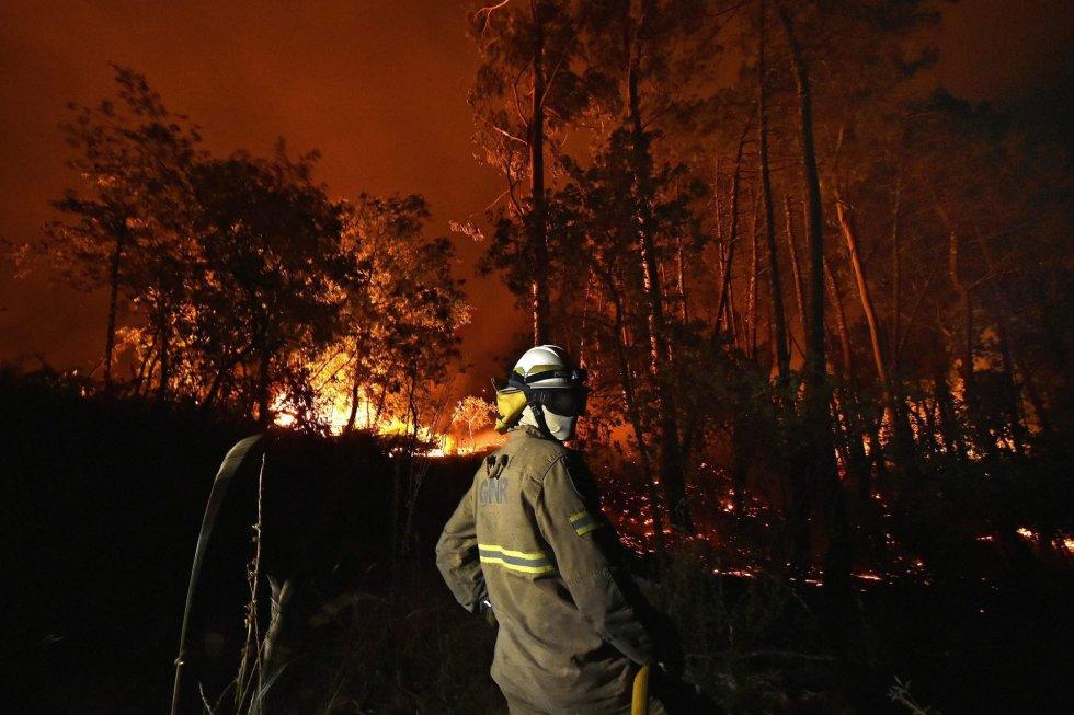 Según la Autoridad Nacional de Protección Civil portuguesa, que monitoriza en su página web en tiempo real la evolución de los incendios, 117 fuegos arden en el país este jueves a mediodía —13 de ellos de grandes dimensiones—. A las 12.30 horas había 3.682 efectivos combatiendo las llamas en Portugal, que cuentan con 1.159 vehículos terrestres y 17 aviones. En la foto, un bombero trabaja en las labores de extinción del incendio forestal que afecta a las localidades de Couto de e Cima y Couto de Baixo en la región de Viseu.