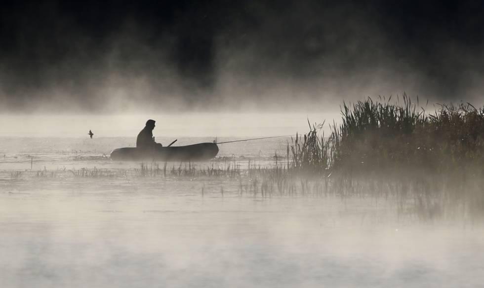 Un hombre pesca desde su bote mientras la niebla le rodea, en el lago de la aldea de Logoisk, al norte de Minsk (Bielorrusia).