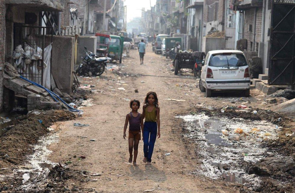 """Niños indios caminan por una calle repleta de basura, en Nueva Delhi (India). Según la Organización Mundial de la Salud, el aire contaminado es una """"emergencia de salud pública"""", ya que nueve de cada diez personas en el mundo respiran aire contaminado."""