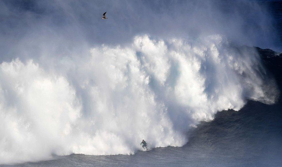 Una persona surfea una ola en Praia do Norte (Portugal).