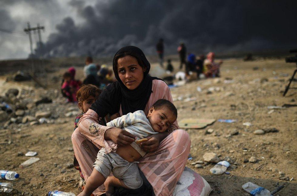 Una madre con dos niños pequeños espera cerca de Qayyarah, tras tener que dejar su hogar a causa del conflicto armado en Mosul.