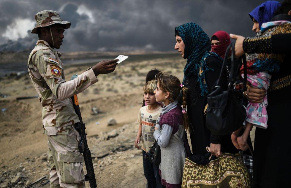 Un miembro de las fuerzas iraquíes habla con familias que han huído de Mosul a Qayyarah. La agencia de refugiados de la ONU se prepara para recibir 150.000 iraquíes que están huyendo en los últimos días de los enfrentamientos alrededor de la ciudad de Mosul.