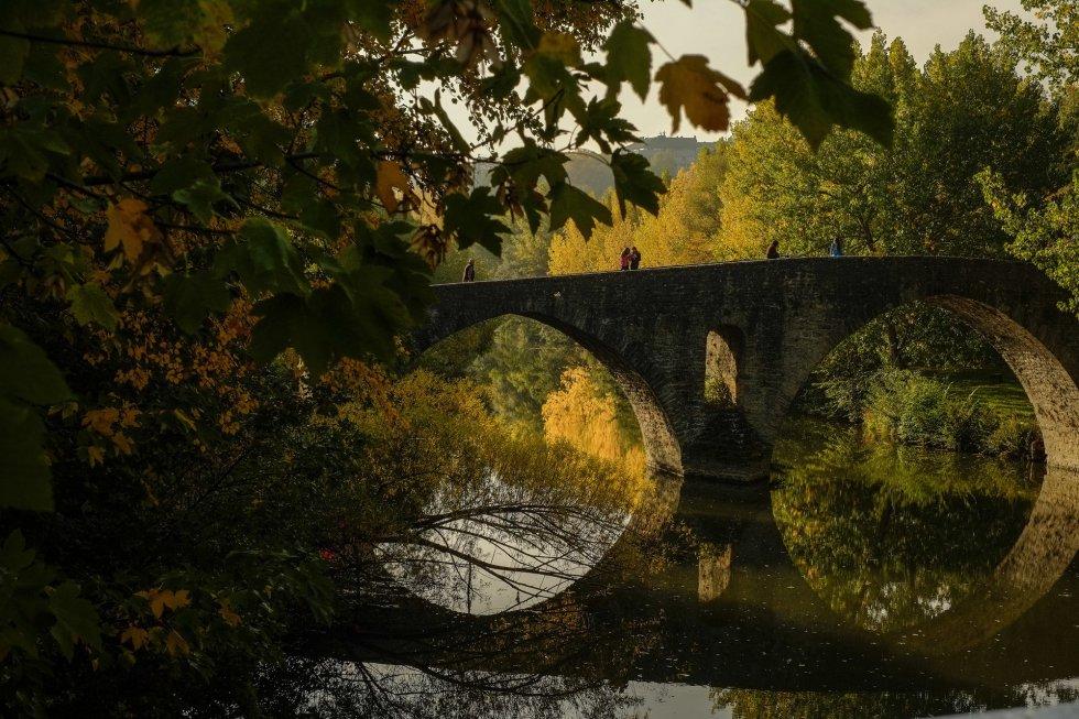 Varias personas pasean por un antiguo puente que cruza el río Arga, en Pamplona.