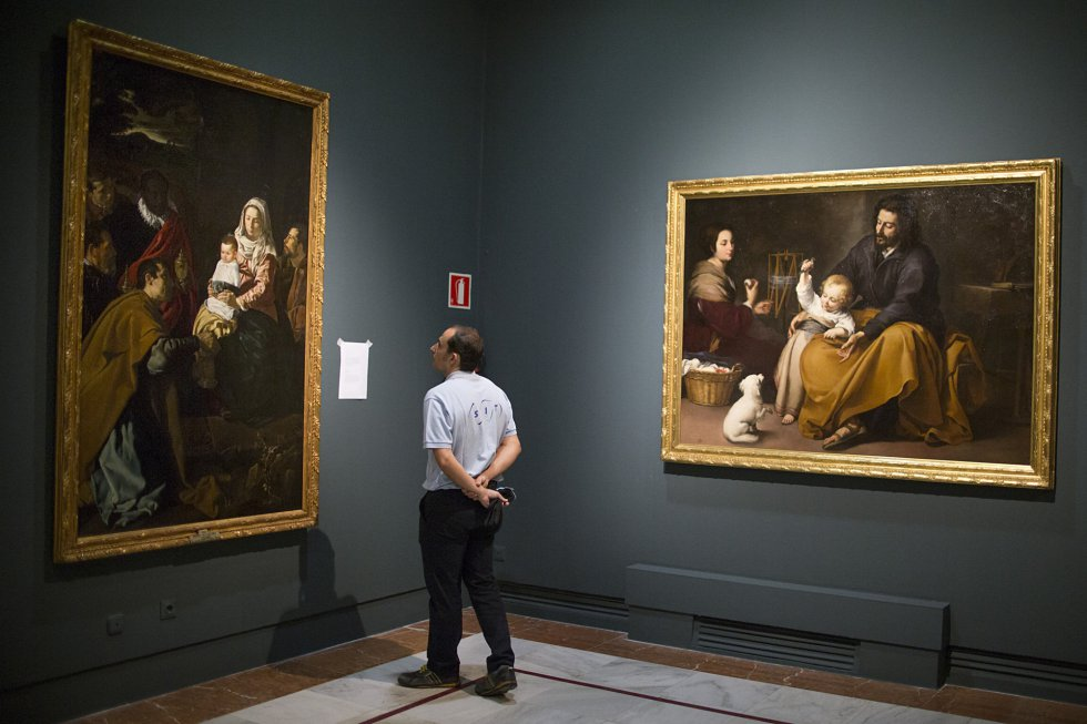 Un técnico mira 'La sagrada familia del pajarito', de Murillo, y 'Adoración de los Reyes', de Velázquez, en la Fundación Focus.