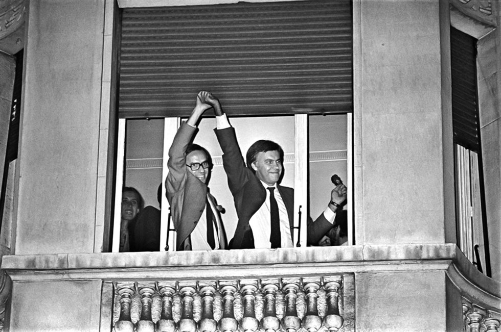 Alfonso Guerra levanta la mano de Felipe González en la ventana del hotel Palace de Madrid para celebrar la victoria del PSOE en las elecciones del 28 de octubre de 1982.