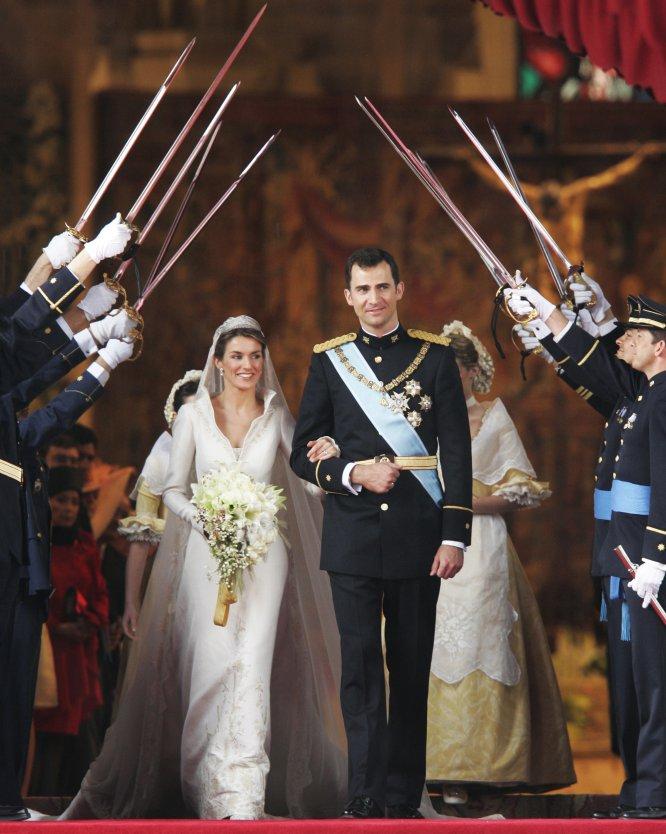 Felipe de Borbón y Leticia Ortiz pasan por el arco de sables de los compañeros de promoción del príncipe tras su boda en la catedral de la Almudena, de Madrid, el 22 de mayo de 2004.