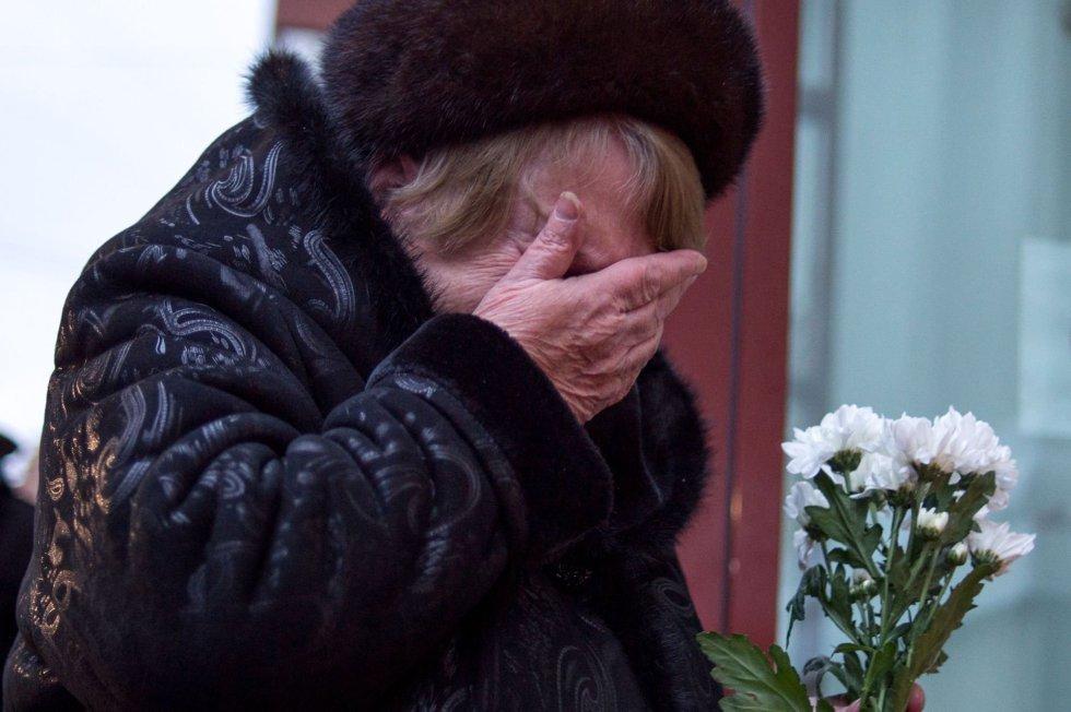 """Además de los artistas del Alexándrov, viajaban a Siria militares, nueve periodistas y la presidenta de la fundación """"Ayuda Justa"""", la doctora Elizaveta Glinka, una conocida filántropa rusa que acompañaba una carga humanitaria destinada a un hospital sirio. En la imagen, una mujer llora tras rendir un homenaje a las víctimas del avión ruso en Moscú."""