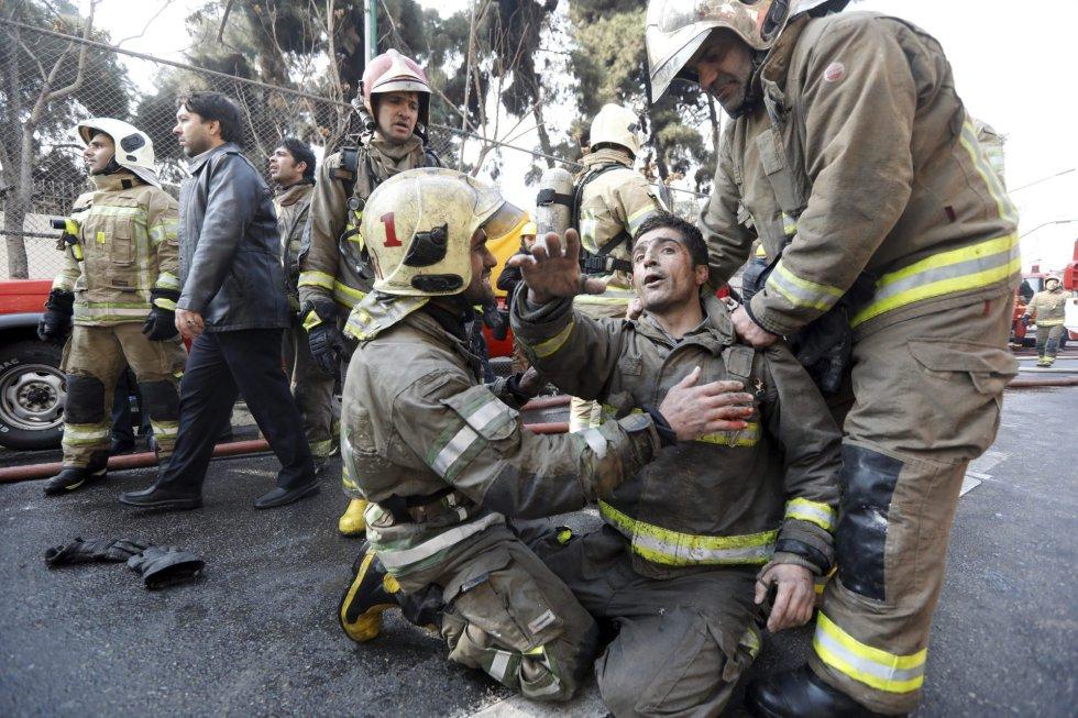 Bomberos iraníes trasladan a un compañero que lograron rescatar tras quedar atrapado entre los escombros del edificio Plasco de la capital de Teherán.