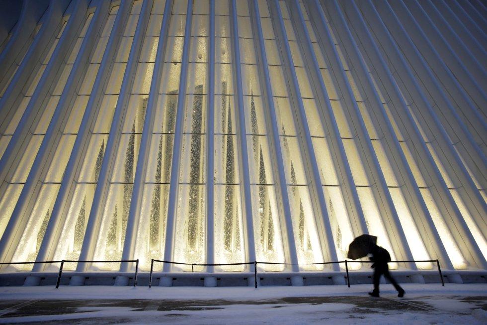 Un hombre se abre camino entre el viento y la nieve frente al Oculus del World Trade Center Transportation Hub, en Nueva York.