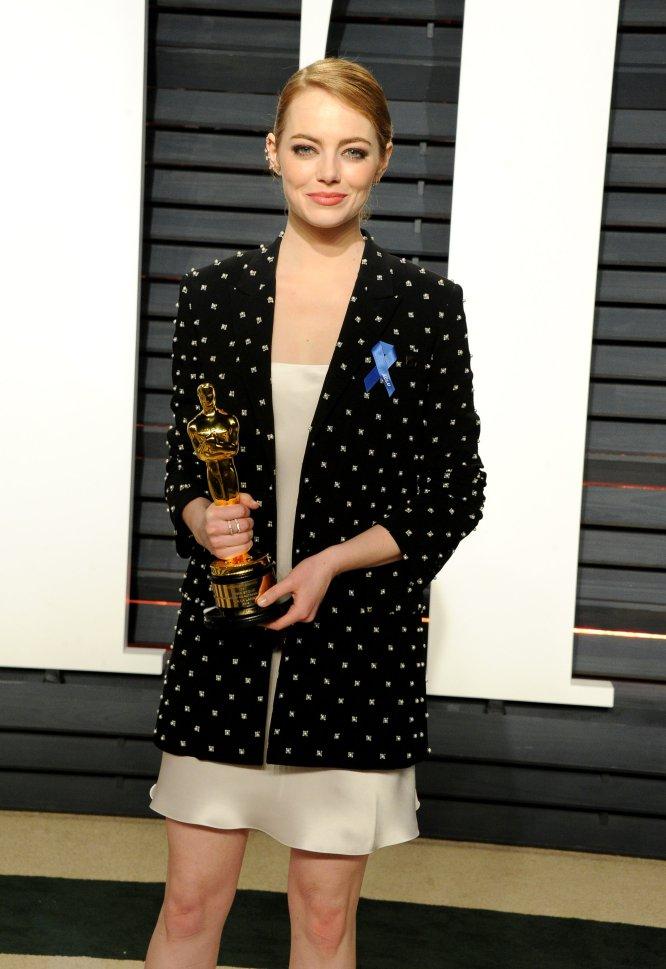 Emma Stone, ganadora del Oscar a Mejor Actriz, eligió para la fiesta 'Vanity Fair' un vestido lencero y una 'blazer' que dejaba a la vista el lazo azul por la lucha de los derechos civiles.