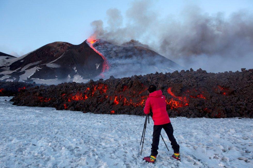 En la imagen, un fotógrafo capta con su cámara una imagen del volcán siciliano Etna, que ha entrado en erupción, cerca de la ciudad de Catania (Italia).