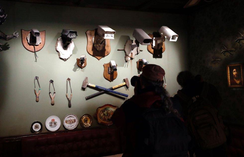 Algunos visitantes toman fotos de las instalaciones de Banksy en el vestíbulo del recién inaugurado hotel.