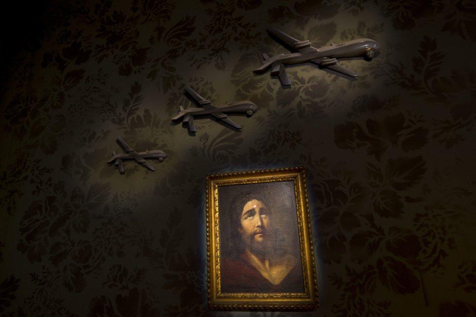 En la imagen, se muestra una pared decorada con una pintura de Jesús. En su rostro, se observa un punto que corresponde al haz de luz que emite un arma de largo alcance. Encima del cuadro, sobrevuelan unos aviones militares.