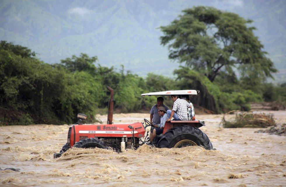 Varias personas subidas en un tractor cruzan el río de Zana cerca de la ciudad de Chiclayo (Perú), el 19 de marzo de 2017.