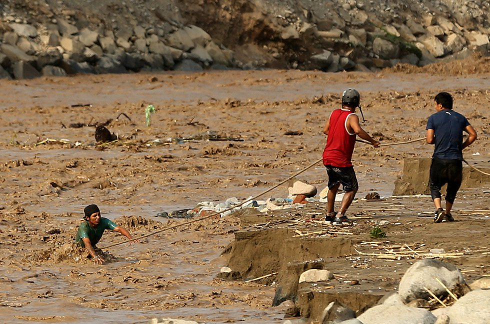 Sin esperar a las nuevas lluvias que se avecinan, el Gobierno peruano, cuyos ministros están repartidos por las distintas zonas de emergencia, se afana por repartir más de 2.000 toneladas de ayuda humanitaria entre los más afectados, mientras las víctimas y los daños siguen aumentando. En la imagen, dos hombres rescatan a una persona atrapada en el Río Rimac en Huachipa (Perú), el 19 de marzo de 2017.