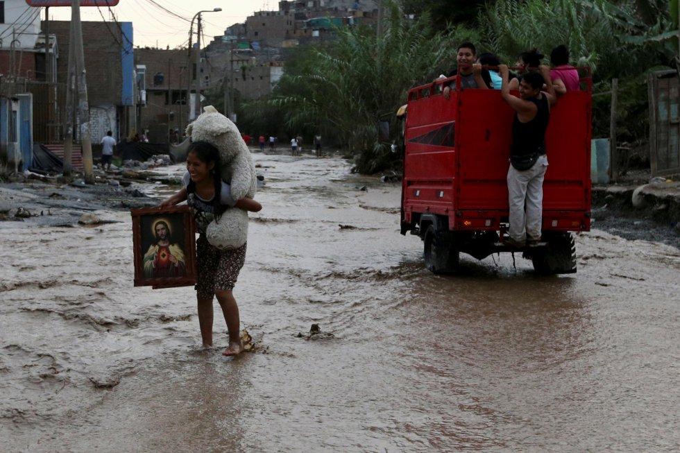 En Lima hay distritos que llevan cerca de tres días sin suministro de agua. En la imagen, una mujer rescata parte de sus pertenencias en Huachipa, distrito de Lima (Perú), el 17 de marzo de 2017.