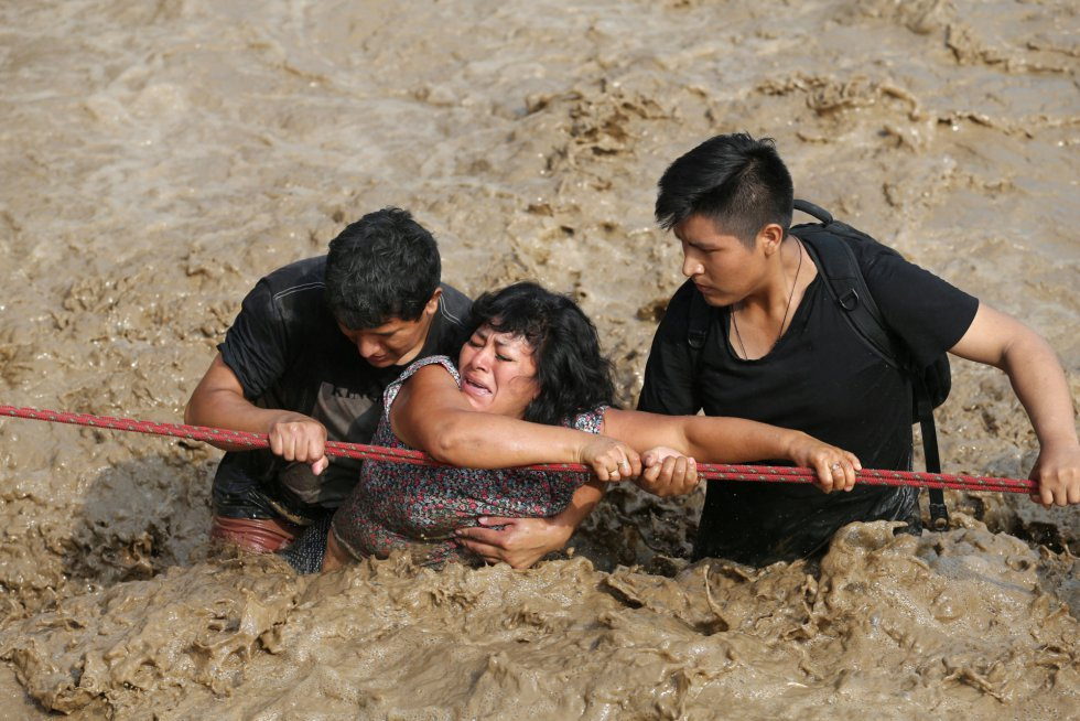 Un nuevo frente de lluvias pronosticado sobre los Andes de Perú amenaza con agravar las consecuencias de las inundaciones sufridas en las últimas semanas, que ya dejan 75 muertos, 263 heridos, 20 desaparecidos, unos 100.000 damnificados y 630.000 afectados. En la imagen, una mujer es ayudada a cruzar una calle inundada en Huachipa (Perú), el 17 de marzo de 2017.