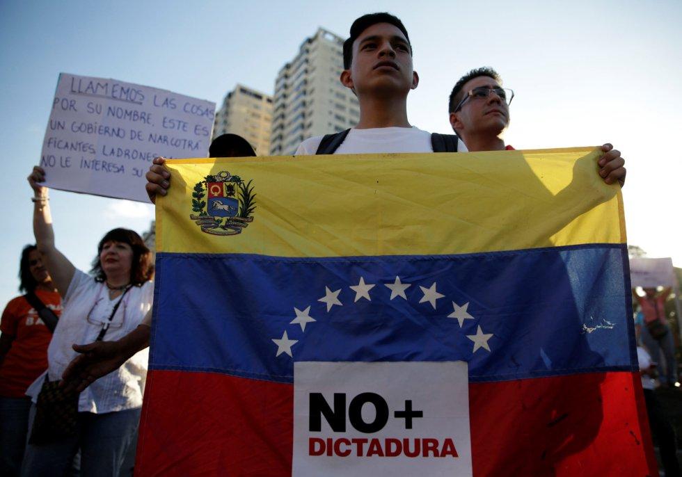 """Un partidario de la oposición tiene una bandera venezolana con una señal que dice """"No más dictadura"""" durante una protesta contra el gobierno del presidente venezolano Nicolás Maduro, en Caracas, Venezuela."""