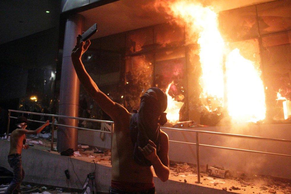 Uno de los asaltantes se toma una foto frente al Parlamento en llamas.