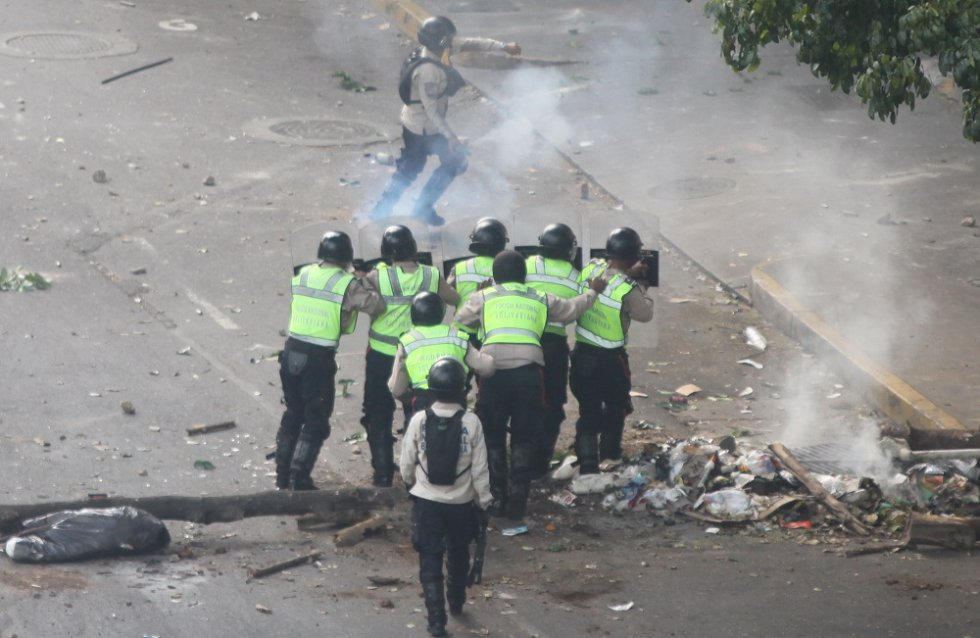 Esta secuencia fue captada durante las protestas de la oposición contra el Gobierno de Nicolás Maduro el pasado 8 de abril en Caracas, capital de Venezuela, en la avenida Francisco Solano, entre los municipios Chacao y Libertador, este último gobernado por el dirigente chavista Jorge Rodríguez. Las fotografías, tomadas desde el mismo ángulo, muestran la intervención de las fuerzas de seguridad en la movilización y su proximidad a los grupos armados afines al oficialismo. En la imagen, un grupo de oficiales de la Policía Nacional Bolivariana se enfrenta a manifestantes opositores.