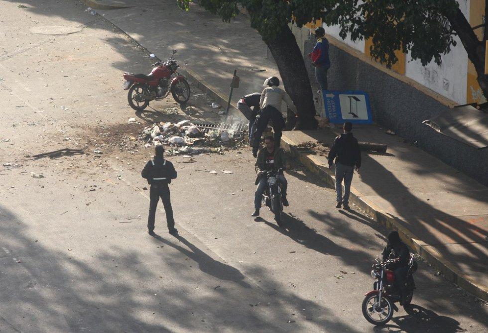 Los civiles armados y un oficial de la policía comienzan a retirar escombros de la vía pública después de reprimir a los manifestantes.