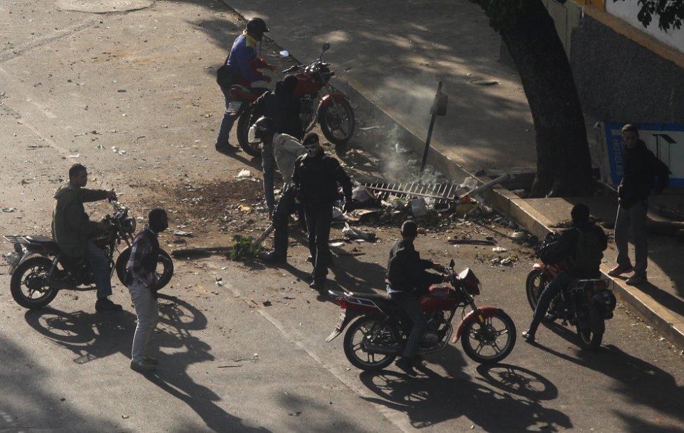 Uno de los hombres armados que ha dispersado la protesta opositora exhibe una máscara parecida a la empleada por policías venezolanos durante la Operación de Liberación del Pueblo, un plan de seguridad ciudadana criticado por vulnerar derechos en Venezuela.