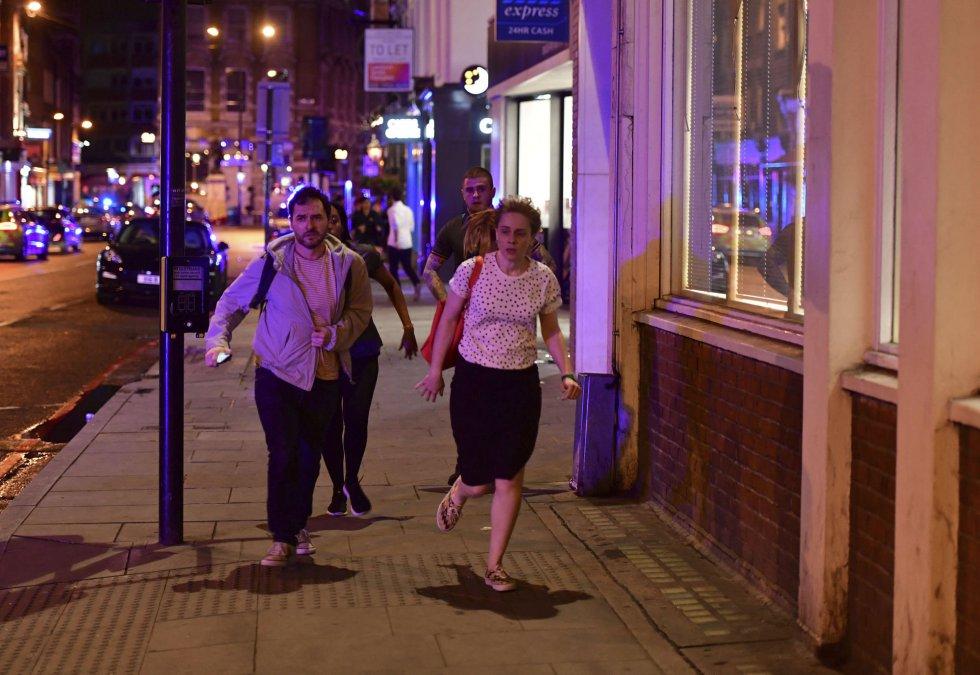 La gente corre por Borough High Street mientras la policía esta investigando cerca del London Bridge.